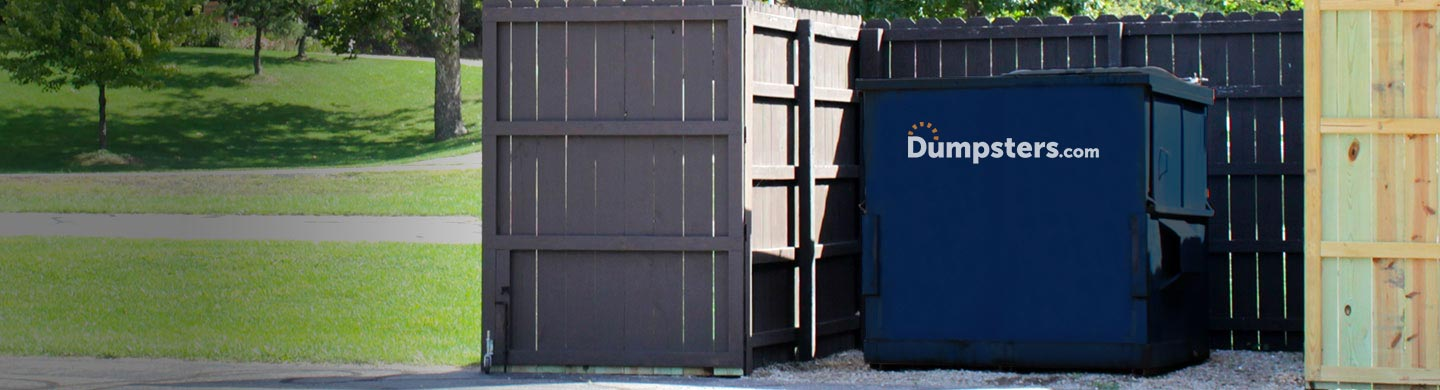 blue front load bin inside a dumpster enclosure in a park