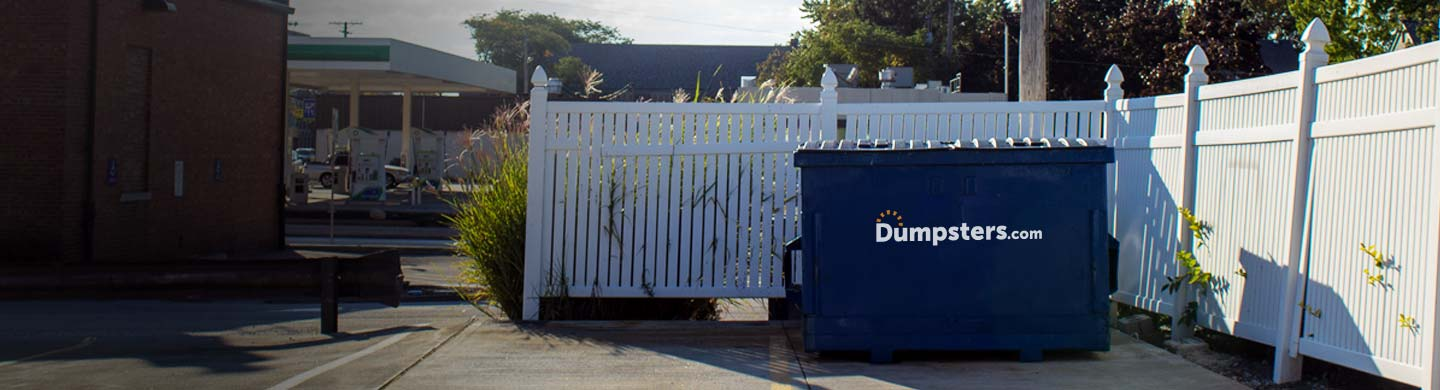 commercial dumpster in front of white fence enclosure