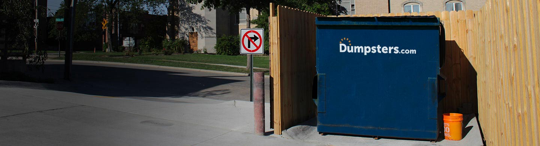 Blue Front Load Bin In a Wooden Enclosure Near Parking Lot.