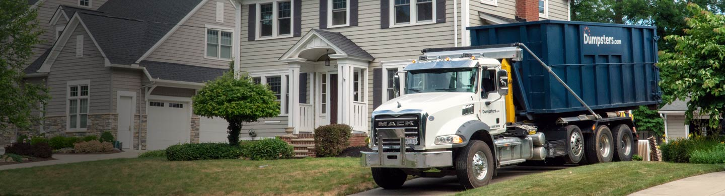 Truck Delivering a Dumpster to a Residential Driveway