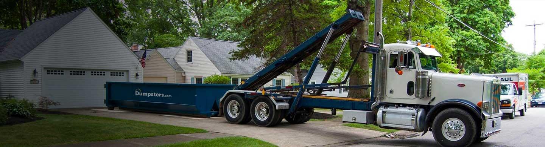 truck unloading roll off dumpster in driveway