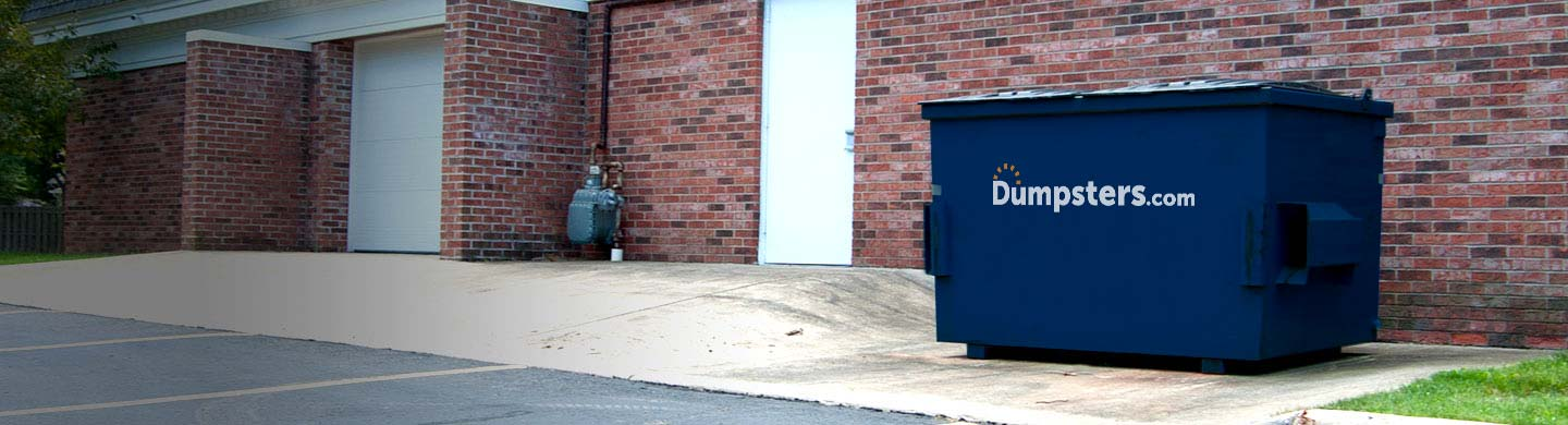 A Blue Front Load Bin Sits Behind a Retail Shop.