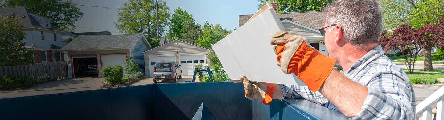 man with orange work gloves throws wood into a dumpster