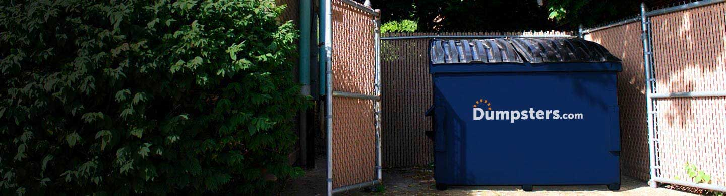permanent dumpster in an enclosure attached to a restaurant