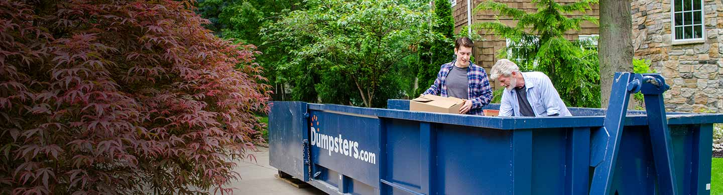 father and son load a roll off dumpster in their driveway