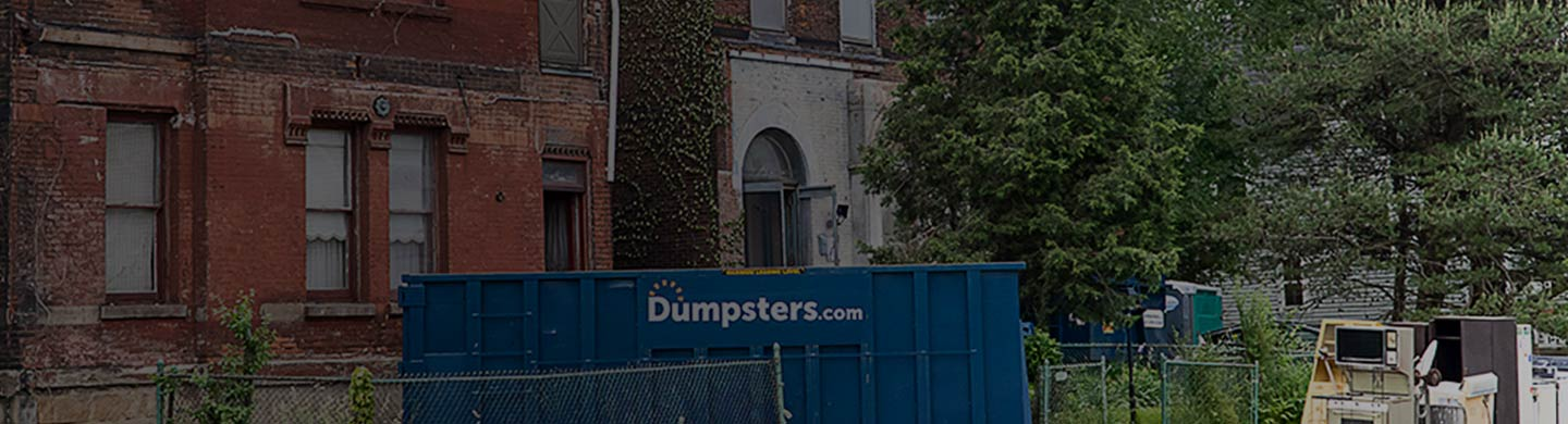 A Dumpsters.com Roll Off Dumpster Outside of a Brick Building.