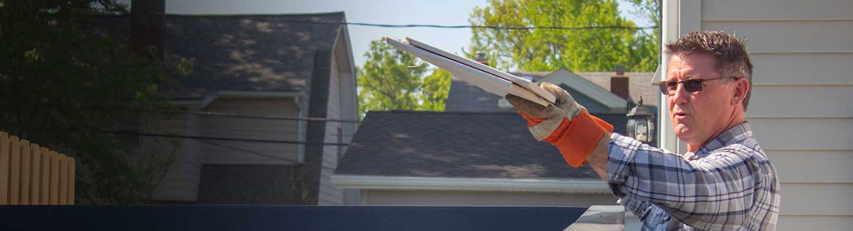 man throwing building materials into a short term dumpster rental
