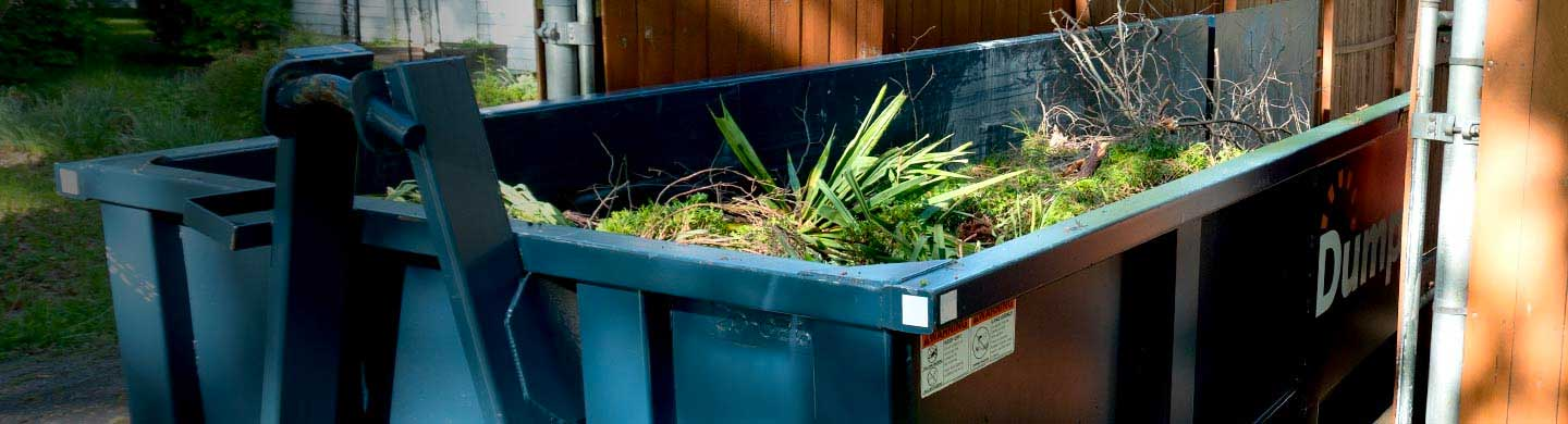 yard waste dumpster partially filled with waste from landscape project