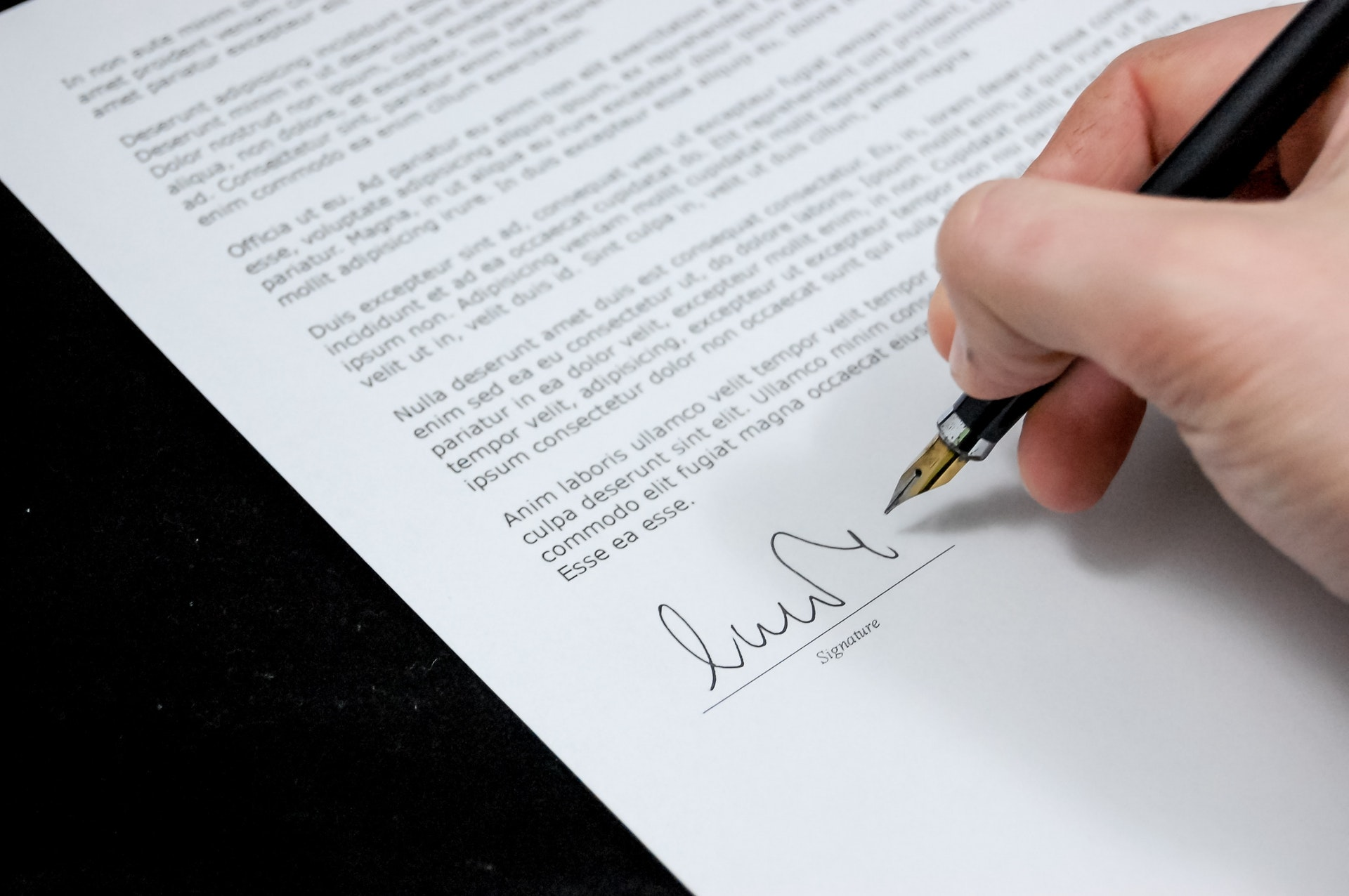 Homeowner writing signature at the bottom of a contract.