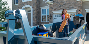 Couple Loading Dumpster With Household Junk.