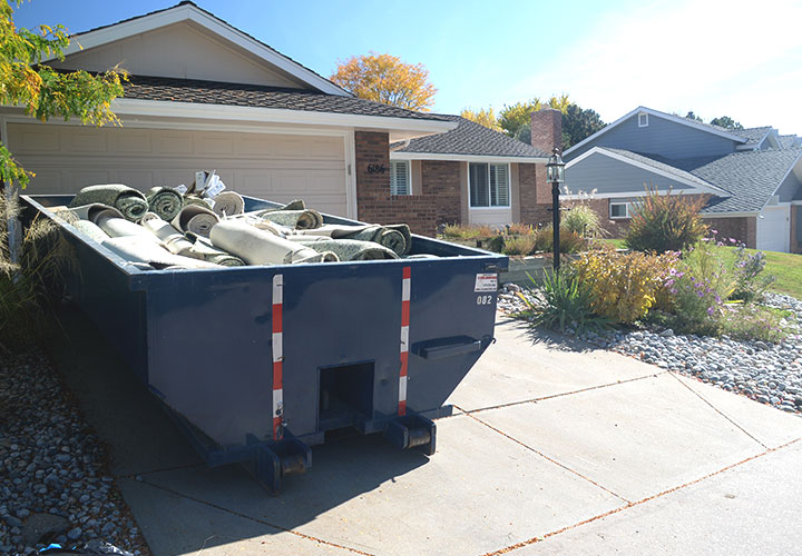 Roll Off Dumpster Near Gravel in Residential Driveway.