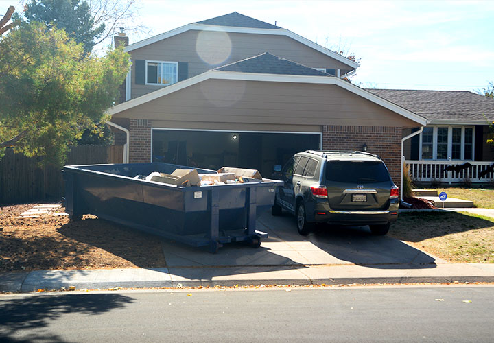 Roll Off Dumpster in Residential Driveway Near House and SUV.