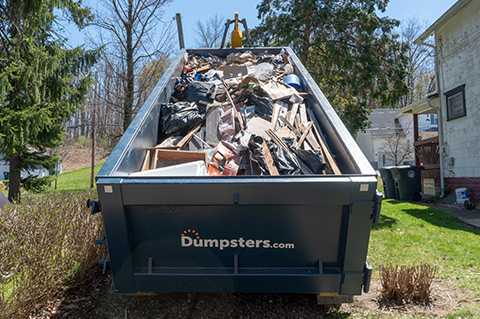 a dumpsters.com roll off dumpster filled with heavy debris