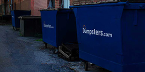 two commercial dumpsters in a back alley