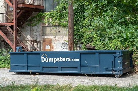 roll off dumpster placed behind an old building with a metal fire escape