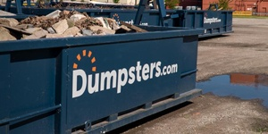 A Blue Dumpsters.com Roll Off Dumpster Filled With Debris.