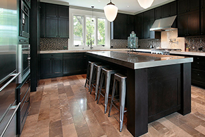 Black cabinetry and stainless steel appliances in a kitchen.
