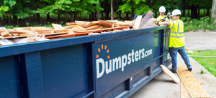 Two Construction Workers Filling a Roll Off Dumpster with Wood.