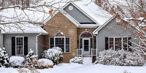 Large suburban home with a front lawn covered in a light snow