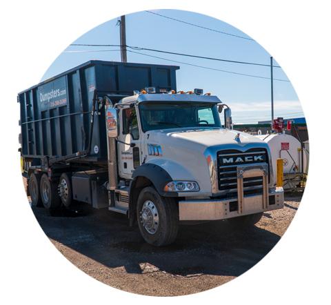 roll off dumpster truck next to a factory gas tank
