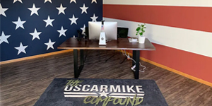 image of a desk on top of rug with the oscar mike compound logo