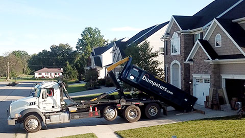 Truck Unloading a Blue Home Dumpster onto a Residential Driveway