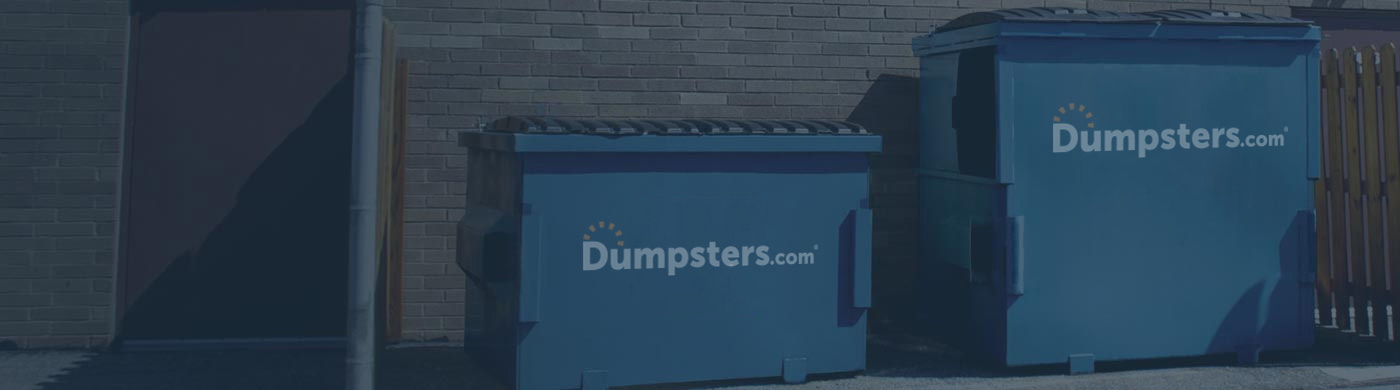 Two Front Load Dumpsters Behind a Building.
