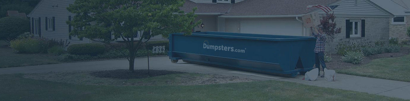 Man Throwing a Box in a Dumpsters.com Roll Off Dumpster.
