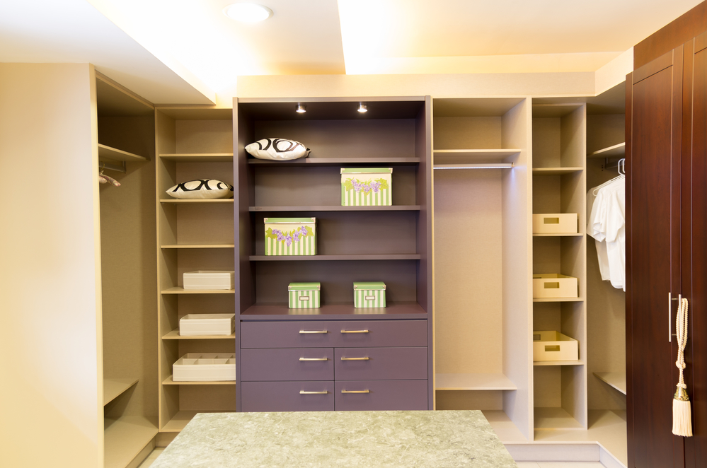 An empty walk-in closet with lots of shelving.