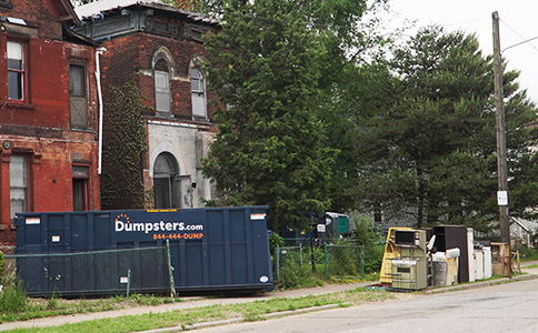 Roll Off Dumpster in Front of Historic Brick Building With Trash on Curb.