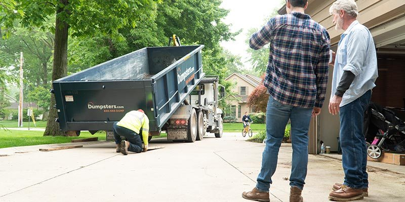 A Dumpsters.com Dumpster Truck Driver Puts Boards on a Driveway as Two Customers Watch.