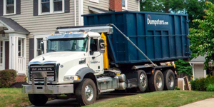 roll off dumpster truck in a driveway near a house