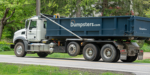 roll off dumpster truck driving down the road