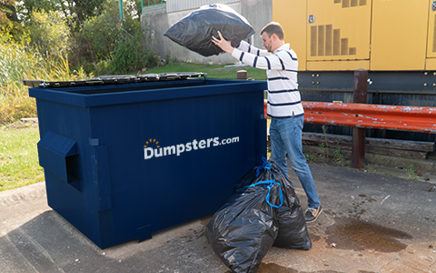 Man Throwing Trash Bags Into Front Load Dumpster.