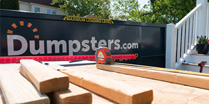 Wood Blocks and Measuring Tape in Front of Dumpsters.com Dumpster.