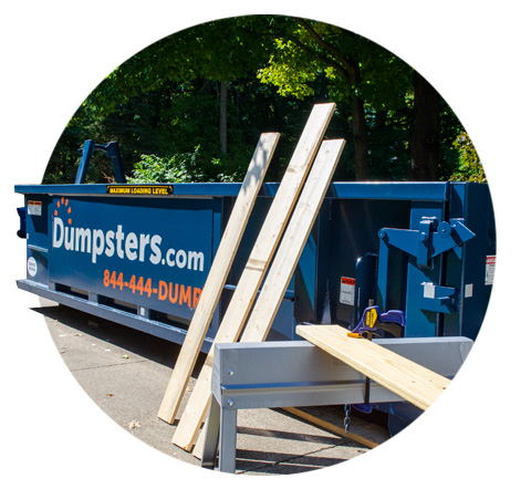 lumber laying against residential construction dumpster