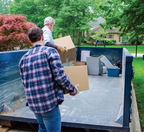 man in blue plaid shirt loading boxes in a dumpster