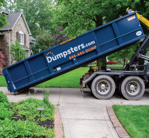 a roll off dumpster being delivered in a homeowner's driveway
