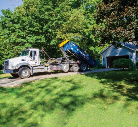 a truck picking up a roll off dumpster