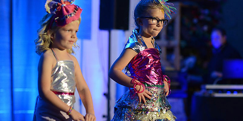 Two Young Models Walk the Runway in Upcycled Dresses at the ScrapsKC ReVision Fashion Show.