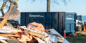 dumpsters.com roll off dumpster with construction debris piled nearby