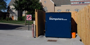 Commercial Dumpster With Wooden Fencing Near a Business