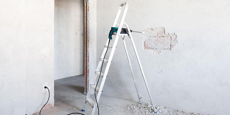 Ladder and Power Chisel Being Used to Remove Drywall in an Empty Room.