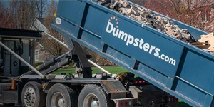 A Blue Dumspters.com Roll Off Dumpster Filled With Heavy Debris.