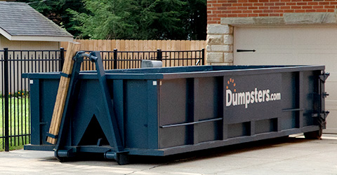Roll Off Dumpster Next to a Black Gate in a Driveway.