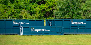 three roll off dumpsters in a green field