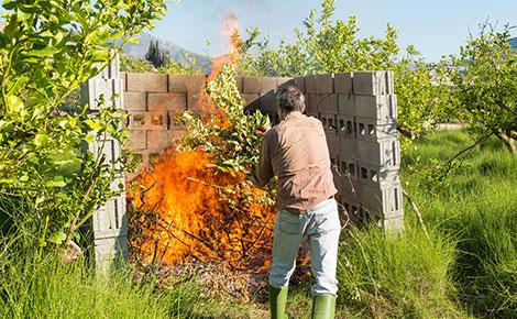 Man Burning Yard Waste in an Enclosed Cinderblock Area.