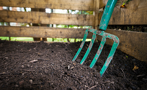Dirt With a Fence and a Gardening Tool.