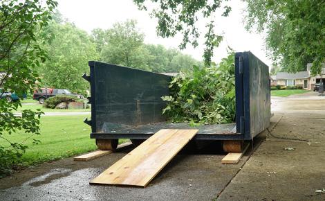A Roll Off Dumpster With Yard Debris Inside.