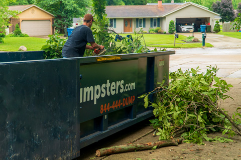 Man Loading Branches in Blue Dumpster.